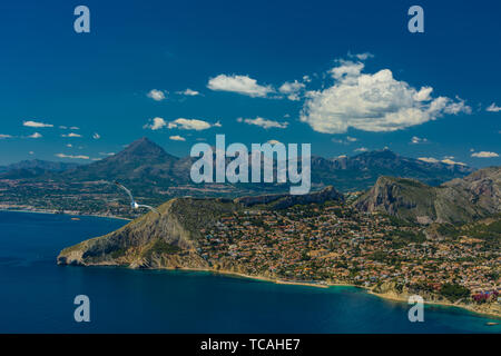 View of the residential area and some of Calpe with the Aitana mountain range at background from the top of the rock of Ifach - Stock Photo