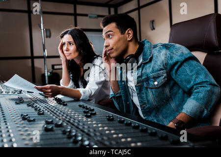 two thoughtful sound producers working at mixing console in recording studio - Stock Photo