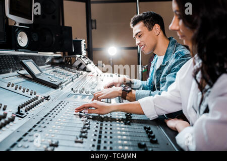 two young multicultural sound producers working at mixing console i recording studio - Stock Photo
