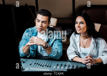 two attentive multicultural sound producers working at mixing console in recording studio - Stock Photo