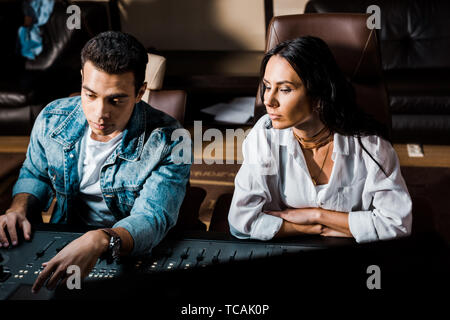 two concentrated multicultural sound producers working at mixing console in recording studio - Stock Photo