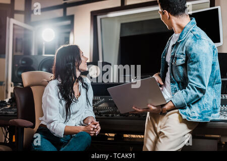two multicultural sound producers working in recording studio together - Stock Photo