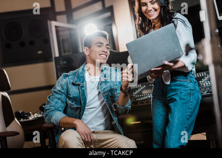 smiling multicultural sound producers using laptop in recording studio - Stock Photo
