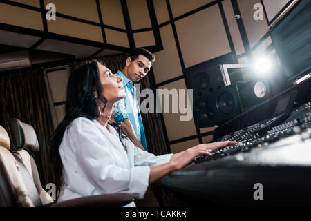 young multicultural sound producers working at sound console in recording studio - Stock Photo