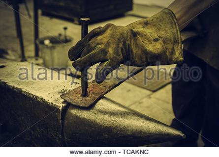Red hot iron in a forge, working with hot iron, traditional work. - Stock Photo