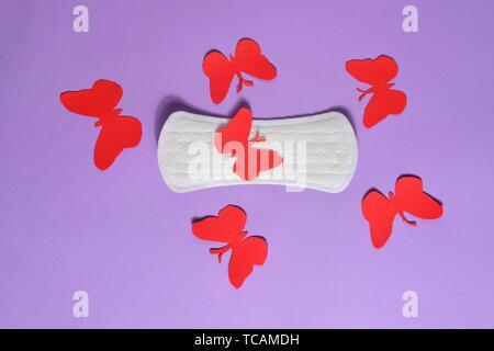 Sanitary napkin for menstruation on violet background. - Stock Photo