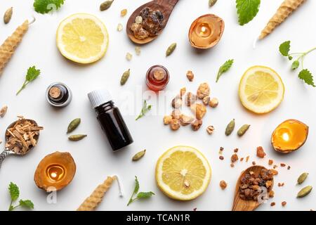 Bottles of essential oil with frankincense, cardamon, melissa, fresh lemon and other ingredients on a white background. - Stock Photo