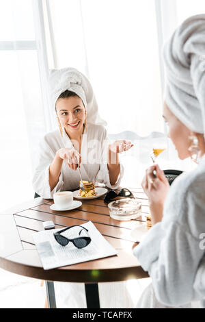 stylish smiling women in bathrobes and jewelry with towels on heads talking while having breakfast - Stock Photo