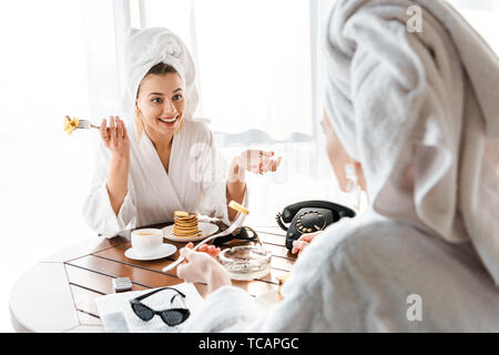 stylish smiling women in bathrobes and jewelry with towels on heads talking during breakfast - Stock Photo
