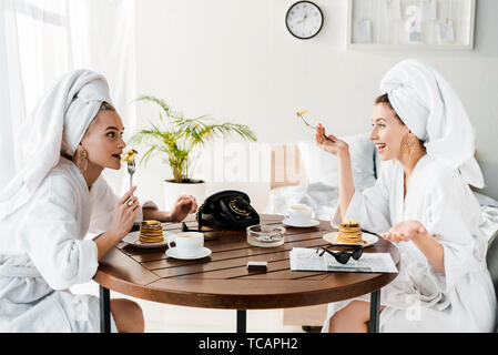 stylish happy women in bathrobes and jewelry with towels on heads talking during breakfast - Stock Photo
