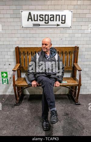 Sophie-Charlotte-Platz U-Bahn Underground railway station on the U2 rail line in Berlin-Charlottenburg.Elderly man on bench waits for train - Stock Photo