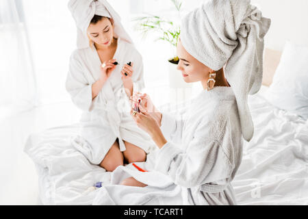 smiling women in bathrobes, towels and jewelry sitting on bed and polishing nails - Stock Photo