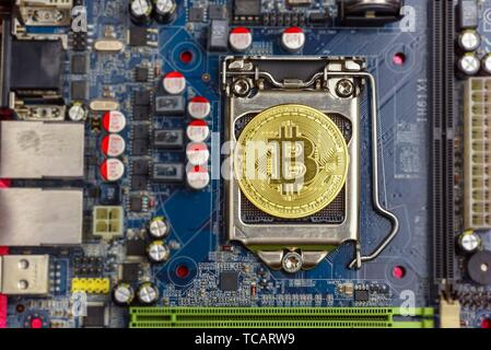 Top view of golden bit coin on computer mother board processor. Bitcoin mining farm, working computer equipment concept. - Stock Photo