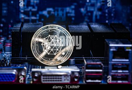 Front view of Qtum cryptocurrency over computer video card. Bitcoin mining farm concept. - Stock Photo