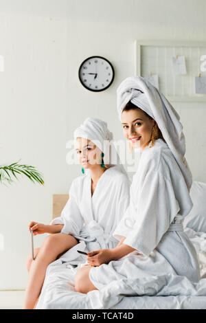 smiling stylish women in bathrobes and jewelry, with towels on heads sitting on bed with nail files and looking at camera - Stock Photo