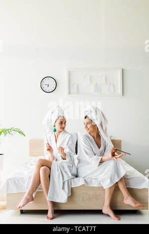 stylish smiling women in bathrobes and jewelry, with towels on heads sitting on bed with nail files - Stock Photo
