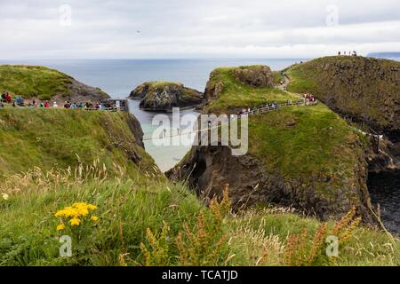 Carrick-a-Rede Rope Bridge is a bridge near Ballintoy in County Antrim, Northern Ireland. The bridge links the mainland to the island of Carrickarede. - Stock Photo