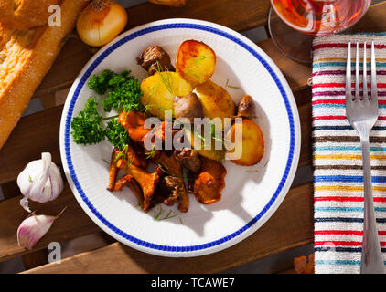 Top view of fried chanterelles served on white plate with baked potatoes and chicken hearts on wooden background - Stock Photo