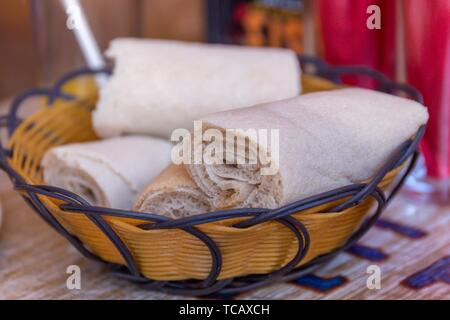 Rolls of Injera in a serving bowl. Injera is a sourdough flatbread made from teff flour. It is the national dish of Ethiopia, Eritrea, Somalia and - Stock Photo