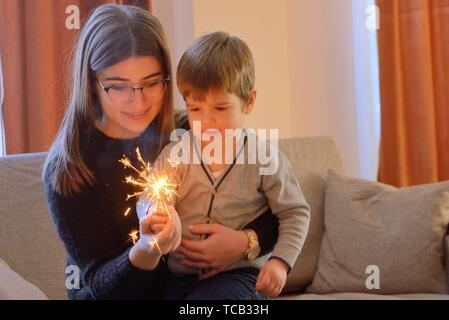Little boy and teen girl holding a sparkler inside of house. - Stock Photo