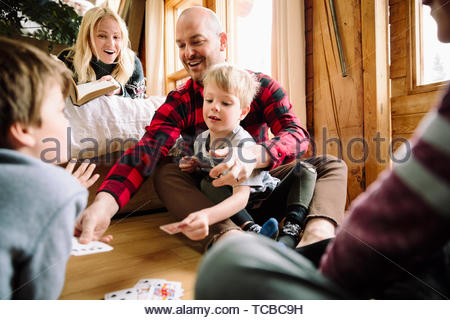 Family playing cards in cabin - Stock Photo