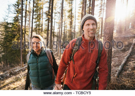 Happy couple hiking in sunny woods - Stock Photo