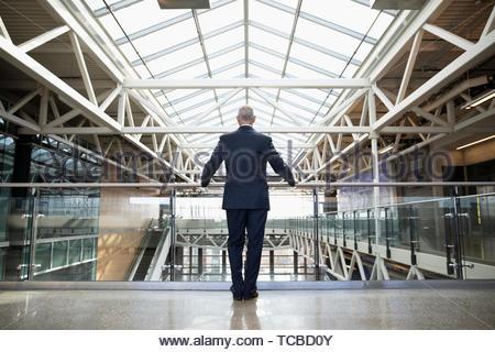 Ambitious senior businessman standing on office atrium balcony - Stock Photo