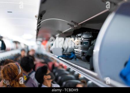 luggage on airplane shelf overhead passenger seat - Stock Photo