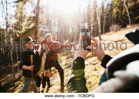 Man with camera phone photographing friends hiking in sunny woods - Stock Photo