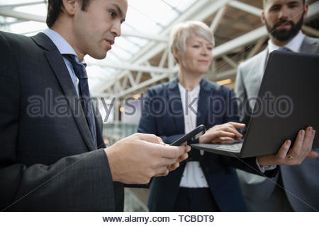 Business people meeting, using laptop and smart phone - Stock Photo