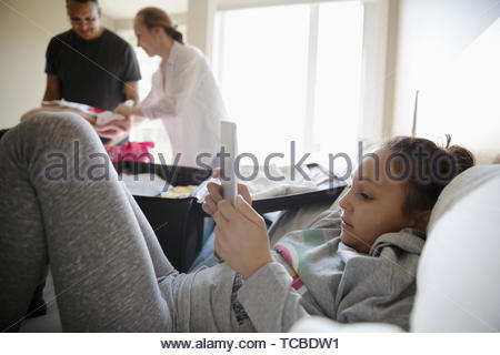Girl using digital tablet on bed while parents pack suitcases for vacation - Stock Photo