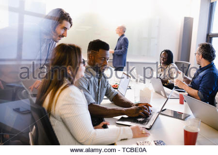 Business people working at laptops and eating take out food in conference room meeting - Stock Photo