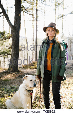 Portrait confident woman with dog hiking in woods - Stock Photo