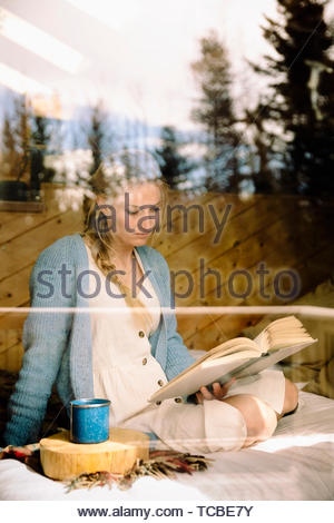 Serene woman reading book and drinking coffee on bed - Stock Photo