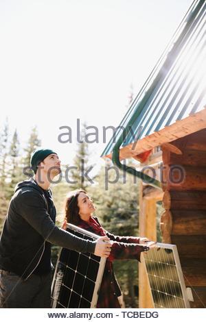 Couple installing solar panels on cabin - Stock Photo