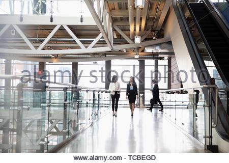 Businesswomen walking and talking on office atrium balcony - Stock Photo
