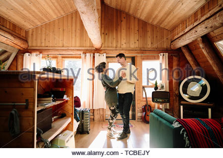 Affectionate couple dancing in cabin - Stock Photo