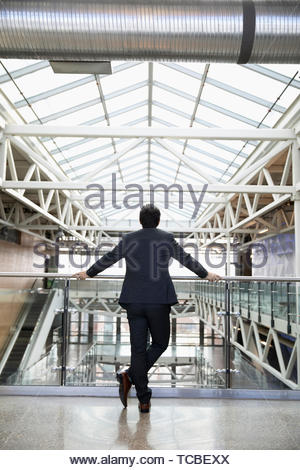 Ambitious businessman standing at office atrium balcony - Stock Photo