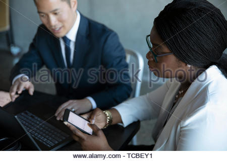 Business people using smart phone and laptop in meeting - Stock Photo