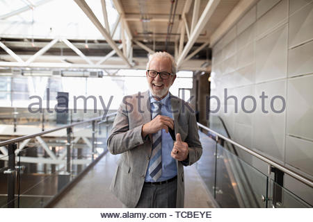Portrait happy, laughing senior businessman in office corridor - Stock Photo
