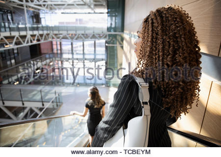 Thoughtful businesswoman descending escalator in office - Stock Photo