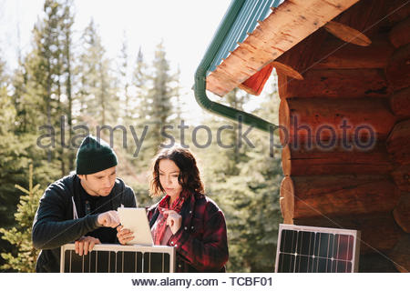 Couple using digital tablet, installing solar panels outside cabin - Stock Photo