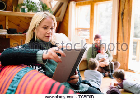 Woman reading book on cabin sofa - Stock Photo