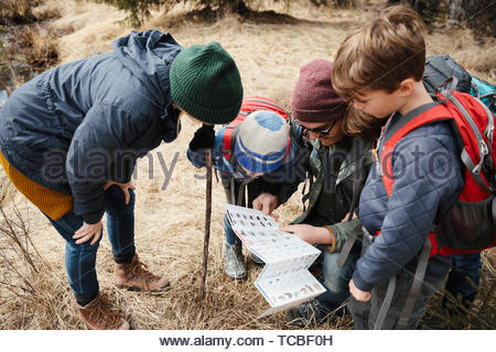 Family hiking, looking at trail guide - Stock Photo