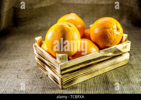 Fresh ripe orange fruits in old burnt wooden crate or box with sackcloth background. Vintage and retro effect added. - Stock Photo