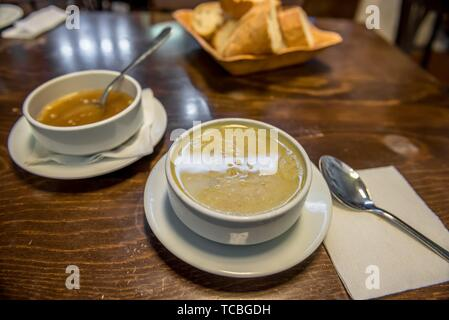 Traditional Turkish hot Tripe Soup with bread and garlic sauce on wooden table. - Stock Photo