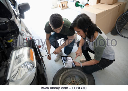 Mother and son with digital tablet learning to change car tire in garage - Stock Photo