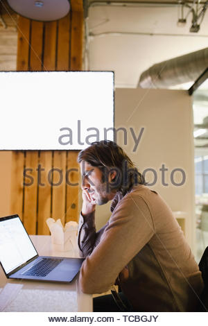 Focused businessman working late at laptop - Stock Photo