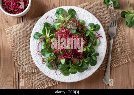Salad with lamb's lettuce and red beet sprouts on a wooden table, top view. - Stock Photo
