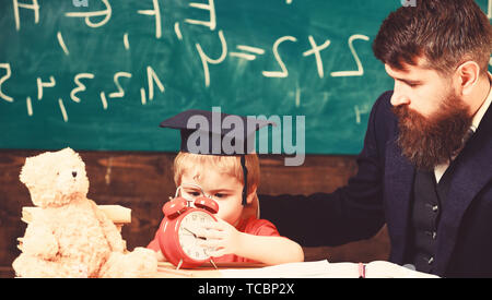 Boy, child on calm face holds alarm clock while teacher talk to kid. Individual lesson concept. Teacher with beard, father teaches little son in classroom, chalkboard on background. - Stock Photo
